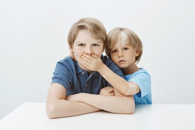 Irmão pedindo para manter segredo. retrato de menino infeliz e irritado sentado à mesa com as mãos cruzadas, franzindo a testa enquanto o irmão cobre a boca com a palma da mão