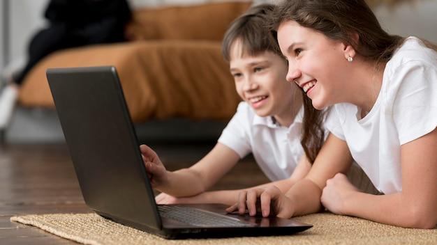 Irmão sorridente olhando para laptop