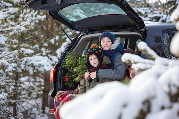 Irmãos adoráveis sentados no carro na floresta de neve de inverno