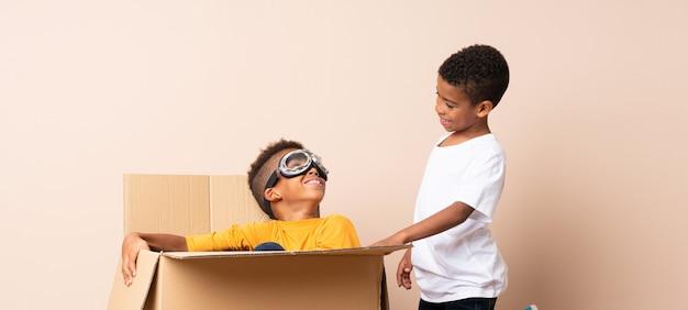 Irmãos afro-americanos jogando. rapaz dentro de uma caixa de papelão com óculos de aviador
