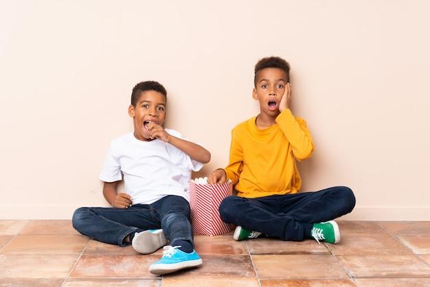 Irmãos afro-americanos segurando pipocas e fazendo o gesto de surpresa