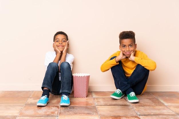 Irmãos afro-americanos segurando pipocas