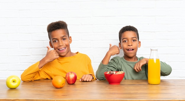 Irmãos afro-americanos tomando café da manhã com o polegar para cima