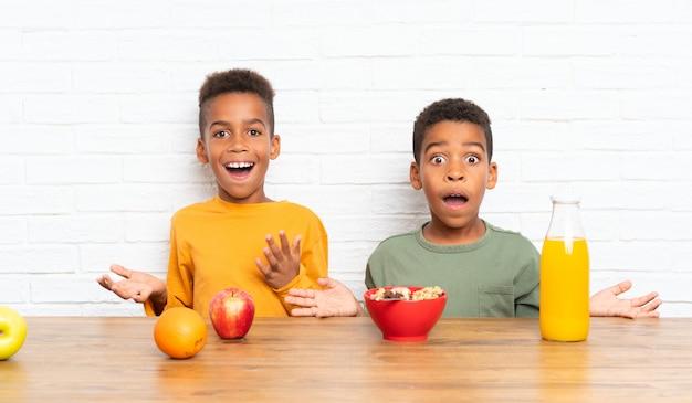 Irmãos afro-americanos tomando café da manhã e fazendo gesto de surpresa