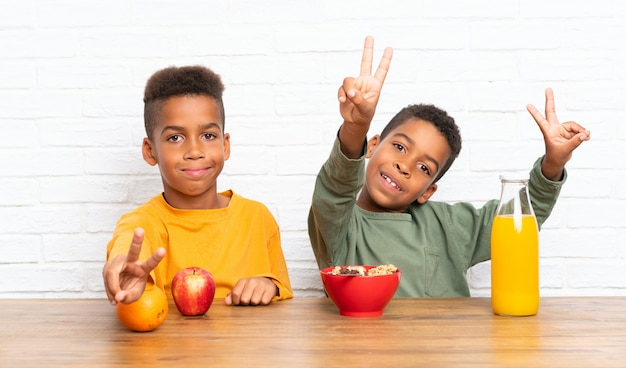 Irmãos afro-americanos tomando café da manhã e fazendo o gesto de vitória