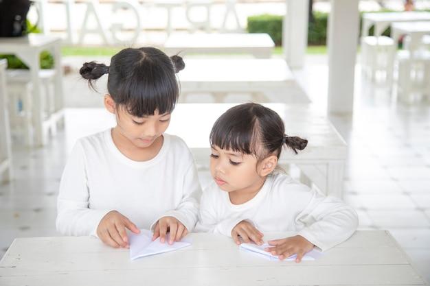 Irmãos asiáticos sentados na mesa criam um avião de papel.