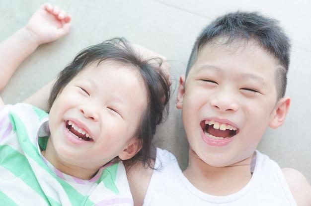Irmãos asiáticos sorrindo no chão