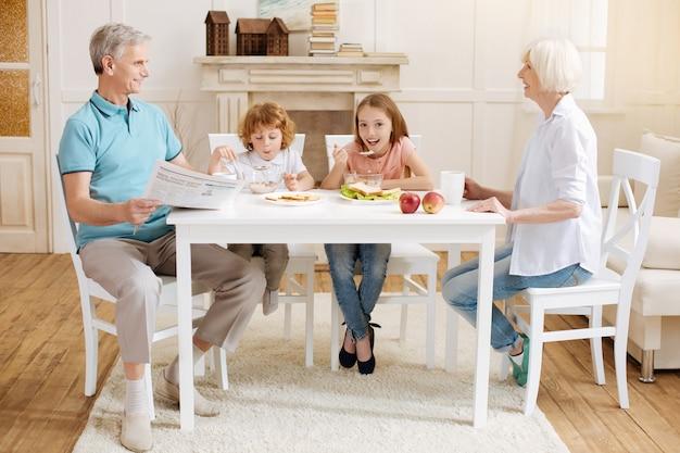 Irmãos ativos positivos e vibrantes sentados à mesa e comendo cereais doces que sua avó os cozinhava pela manhã