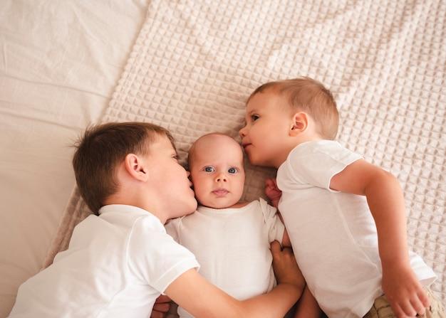 Irmãos beijando bebê recém-nascido vista superior