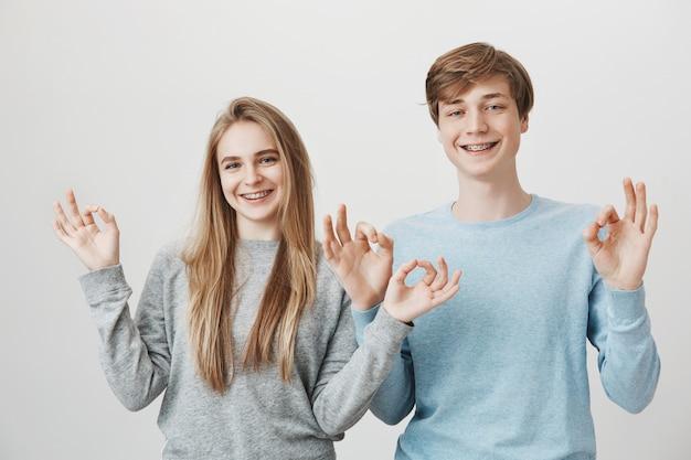 Irmãos bonitos com aparelho, sorrindo feliz e mostram gesto bem