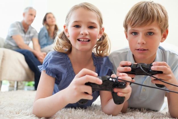 Irmãos brincalhões jogando videogames com seus pais na b