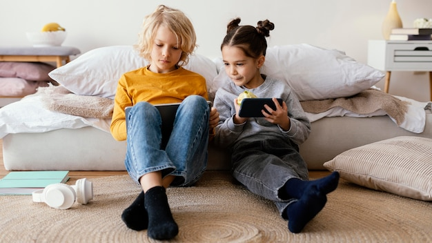 Irmãos brincando com celular e tablet