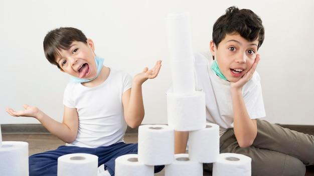 Irmãos brincando com papel higiênico
