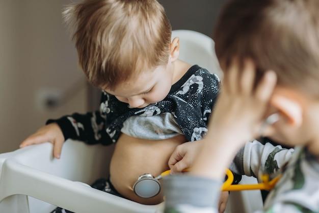 Irmãos brincando de médico e paciente. um menino está estetoscopando outro. imagem com foco seletivo. foto de alta qualidade