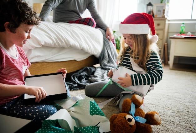 Irmãos caucasianos desembrulhar caixa de presente de natal Foto Premium