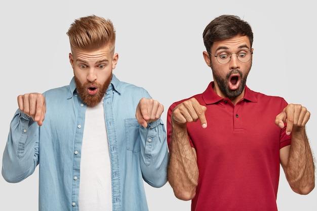 Irmãos caucasianos estupefatos têm um olhar inesperado para baixo, apontam com o dedo indicador no chão e ficam sem palavras de espanto