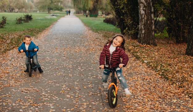 Irmãos caucasianos jovens andando de bicicleta no parque