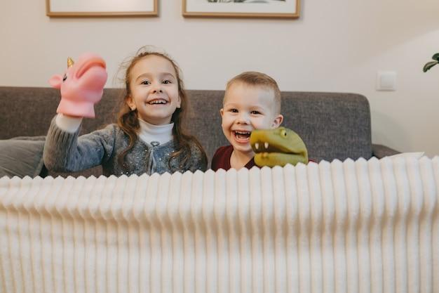 Irmãos caucasianos se divertem juntos enquanto brincam com seus brinquedos imitando personagens do cinema