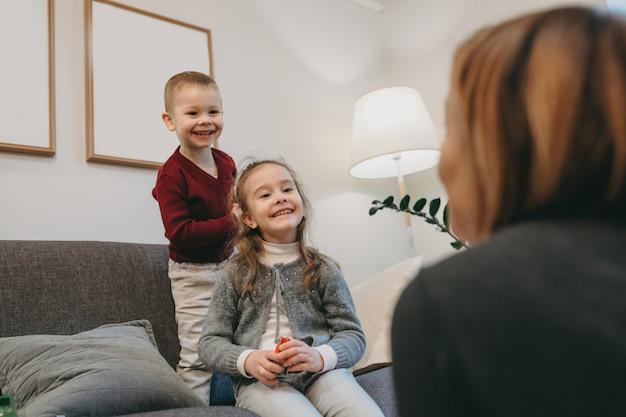Irmãos caucasianos se divertindo com a mãe, sentados no sofá e sorrindo