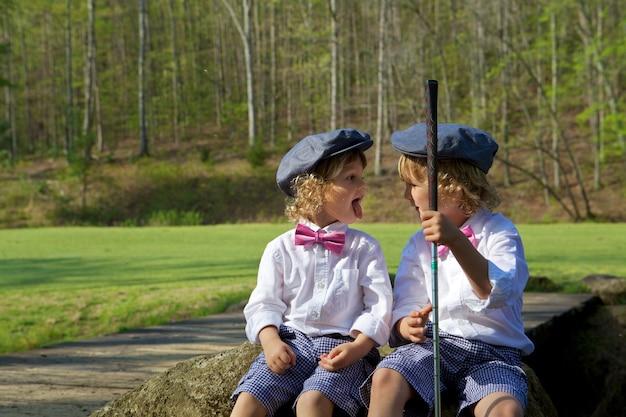 Irmãos com caras engraçadas em um campo de golfe cercado por vegetação sob o sol