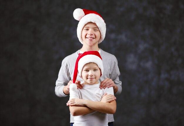 Irmãos com chapéus de papai noel em fundo cinza