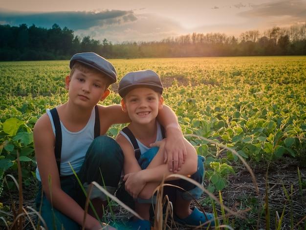 Irmãos com chapéus e suspensórios em um campo coberto de vegetação durante o pôr do sol