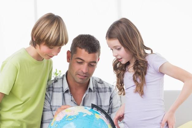 Irmãos com pai explorando o mapa no globo