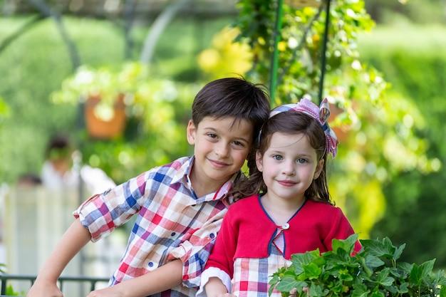 Irmãos com roupas combinando e sorrindo para a câmera rodeada pela natureza