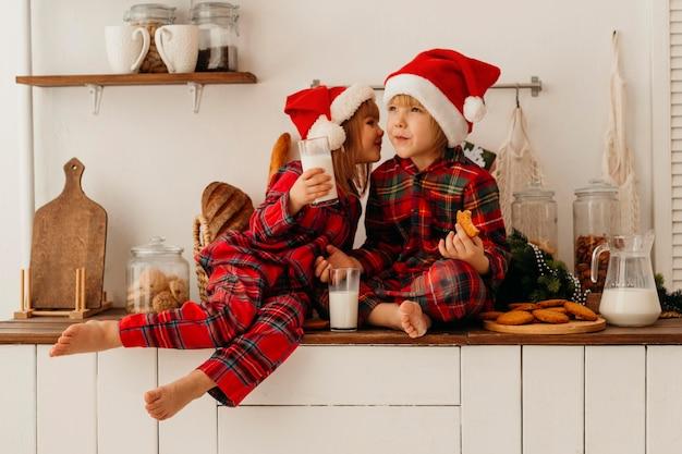 Irmãos comendo biscoitos de natal e bebendo leite