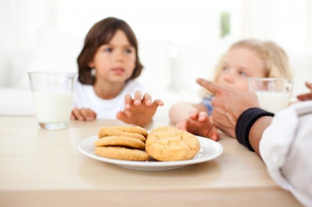 Irmãos comendo biscoitos e bebendo leite