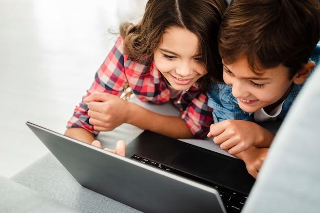Irmãos de alto ângulo em casa usando laptop