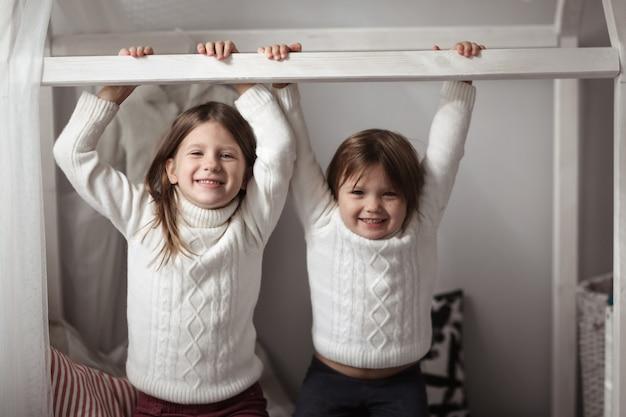 Irmãos de crianças brincam na sala de crianças, interior real