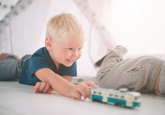 Irmãos de crianças estão deitados no chão. os meninos estão brincando em casa com carros de brinquedo em casa pela manhã. estilo de vida casual no quarto.