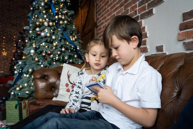 Irmãos de crianças lendo livro perto de uma grande árvore de natal
