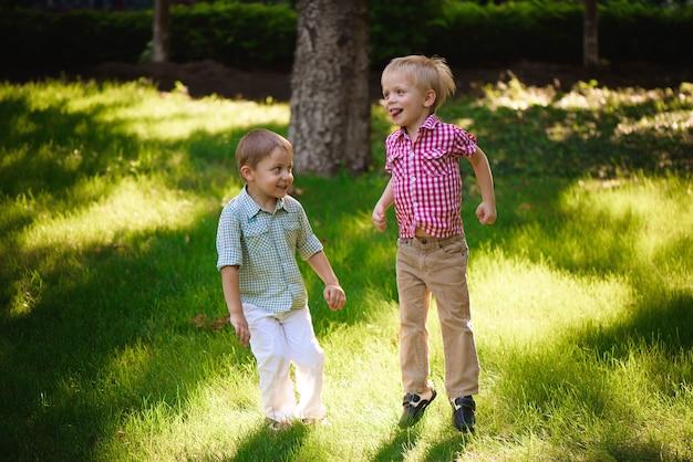 Irmãos de dois meninos brincando e pulando ao ar livre em um parque.