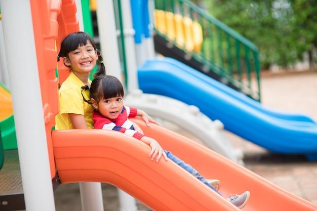 Irmãos de meninas bonitos se divertindo no playground ao ar livre em um dia ensolarado de verão. crianças em slides de plástico. atividade divertida para criança. lazer esporte ativo para crianças