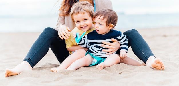 Irmãos de um e três anos na praia na tarde de verão sorrindo com a mãe