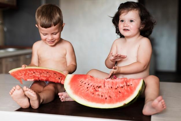 Irmãos de vista frontal com fatias de melancia