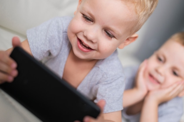 Irmãos de vista frontal jogando em close-up de smartphone