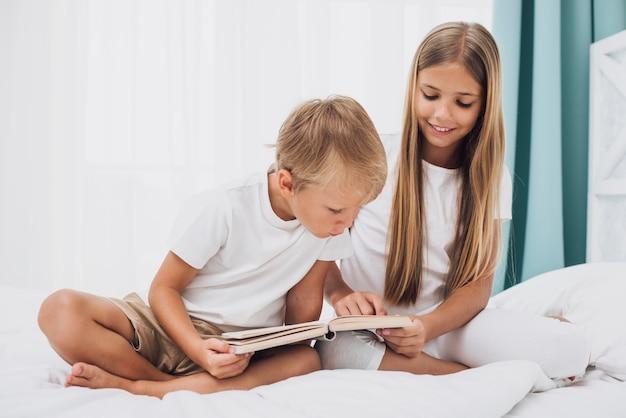 Irmãos de vista frontal lendo juntos um livro