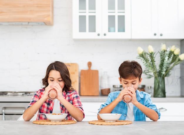 Irmãos de vista frontal na mesa comendo