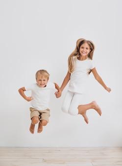 Irmãos de vista frontal pulando juntos