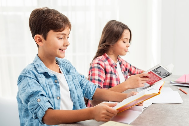 Irmãos de vista lateral estudando o tempo em casa
