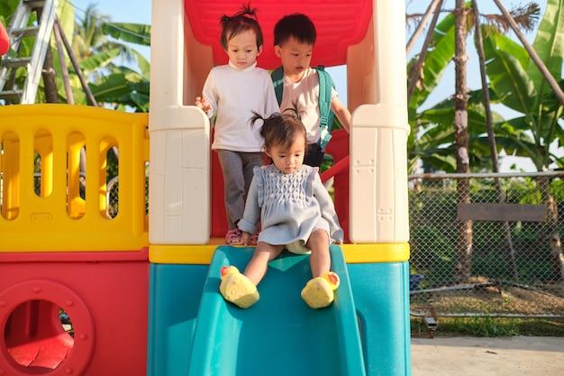 Irmãos e irmãs asiáticos fofos se divertindo brincando em um escorregador no parquinho do quintal de casa