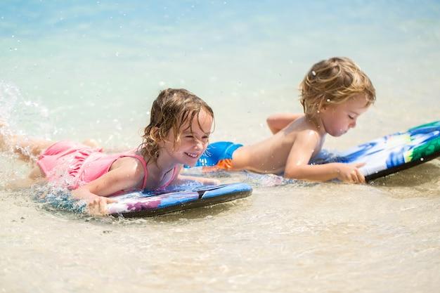 Irmãos e irmãs gêmeos se divertem surfando no oceano