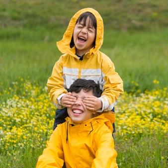 Irmãos em capa de chuva brincando no parque
