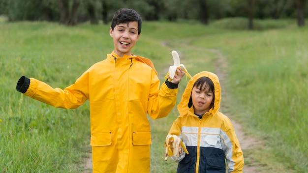 Irmãos em capa de chuva comendo bananas plano médio
