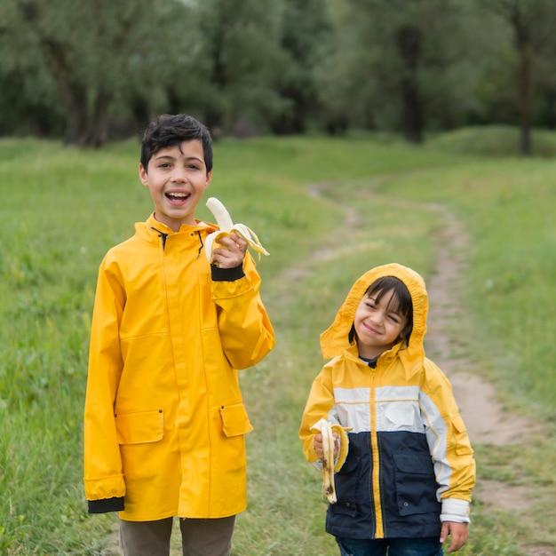 Irmãos em capa de chuva comendo bananas