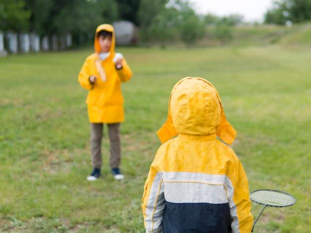 Irmãos em capa de chuva jogando badminton efeito turva