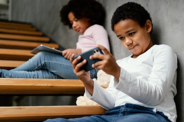 Irmãos em casa usando celular e tablet